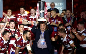 Wigan Warriors manager Shaun Wane hoists the trophy high following their victory.