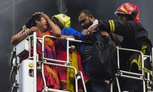 A survivor reacts after being rescued by firefighters from the burning office building.