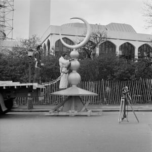 Two men fastening the crescent finial to a crane