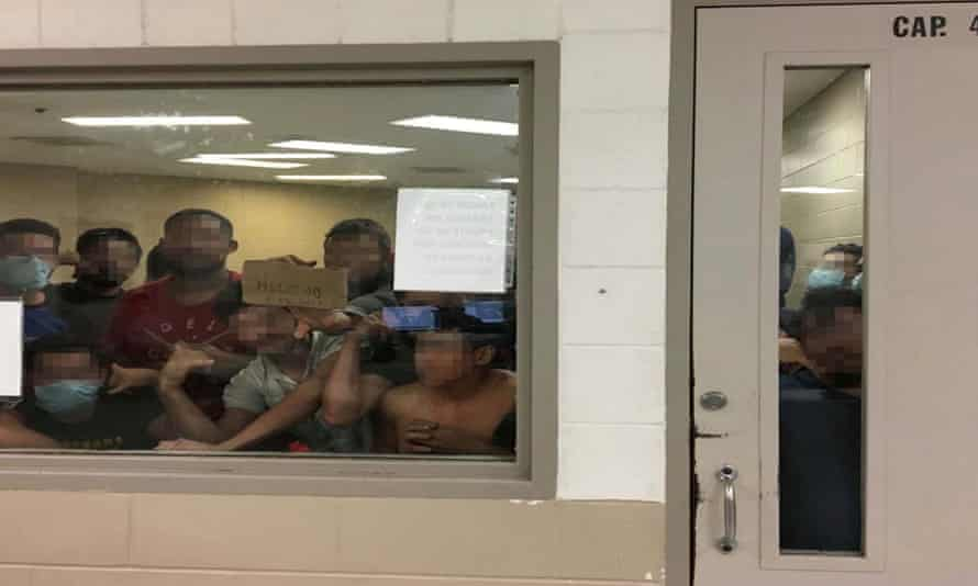 Some of a group of 88 adult males press against the window of a cell built to hold 41 people at Fort Brown border patrol station in Brownsville, Texas.