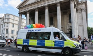 A police van carries rainbow balloons at Pride in London.
