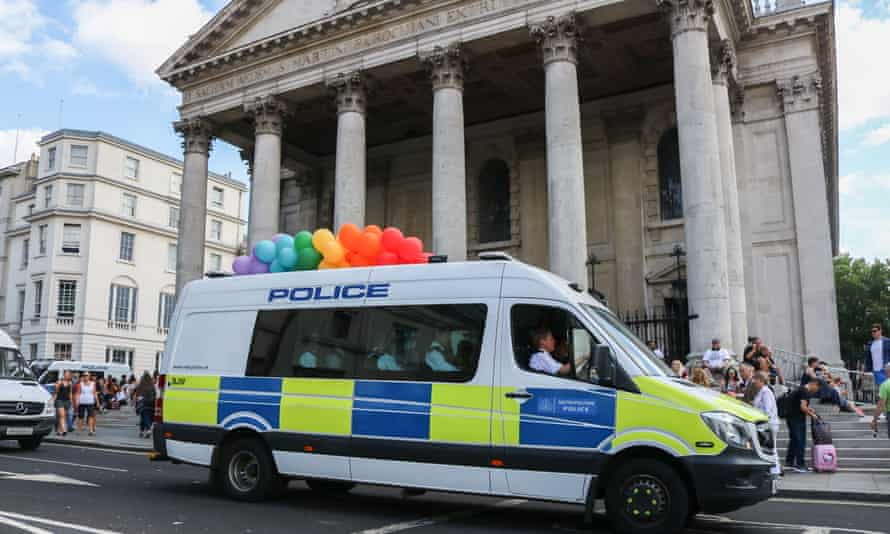 A police van carries rainbow balloons at Pride in London.