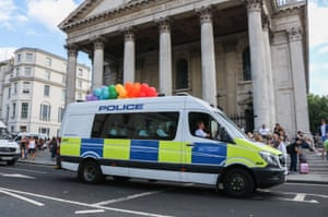 A police van arrives adorned with rainbow balloons ahead of the parade