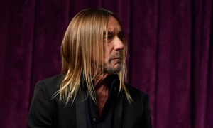 Side-on shot against a plush maroon curtain of the singer with long blond hair and a short beard  looking serious