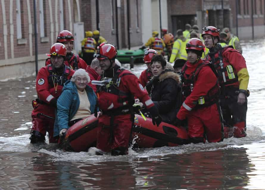 Members of the army and rescue teams help evacuate people from flooded properties in York city centre.