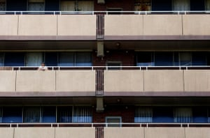 A woman standing on a balcony of a Surry Hills housing commission block