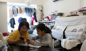 Asa Lai, helps her daughter Caris, 11, with her school work at their home in Hong Kong in September.