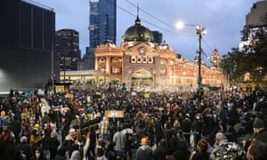Protestors listen to speeches as night falls at the Melbourne Black Lives Matter protest