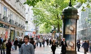 People walking down New Street, a pedestrian street with many shops, Birmingham, UK.