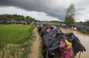 Refugees shelter along a stream as the monsoon rains create massive challenges for the displaced Rohingya in Kutupalong, Cox's Bazar, Bangladesh.