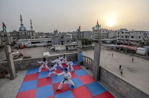 Karate coach Khaled Sheikh el Eid trains with his children on the rooftop of the family home in Rafah