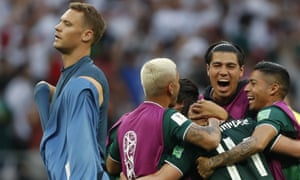 Manuel Neuer walks past as theMexico players celebrate a famous World Cup win against Germany.