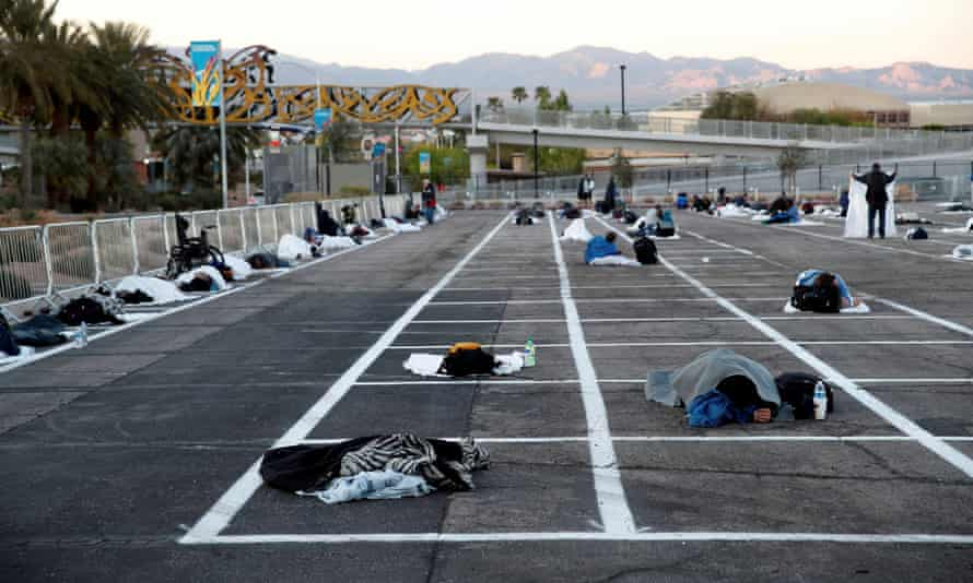 Homeless people sleep in a parking lot with spaces marked for social distancing in Las Vegas.