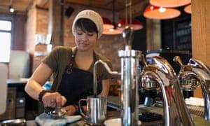 Barista pressing espresso with tamper in coffee shop