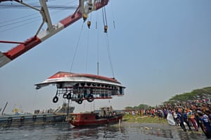 Crowds watch as a capsized boat is recovered from Shitalakshya River