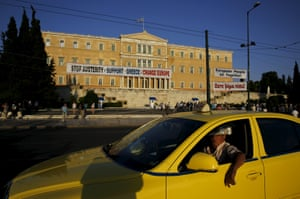 A driver in his taxi passes by the parliament building during a pro-government rally calling on Greece's European and International Monetary creditors to soften their stance in the cash-for-reforms talks in Athens, June 17, 2015. The Greek central bank warned on Wednesday that the country risked a painful exit from the euro and ultimately even the European Union if Athens and its creditors do not strike a swift aid-for-reforms deal. REUTERS/Yannis Behrakis