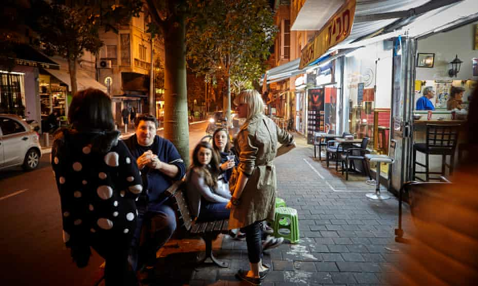 Itamar Srulovich (second left), co-owner of Honey & Co, eating streetside falafel in Tel Aviv.