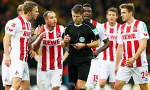 Cologne players argue with the referee, Patrick Ittrich, after the controversial decision.