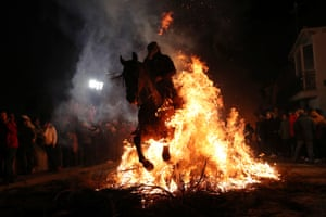 A person rides a horse through flames during the annual Luminarias celebration on the eve of Saint Anthony's day, Spain's patron saint of animals.