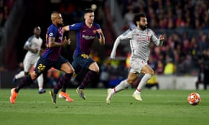 Mohamed Salah of Liverpool goes past Barcelona's Arturo Vidal (left) before being pulled back by Clement Lenglet.