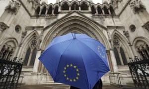A person under an EU flag umbrella outside the high court in London.