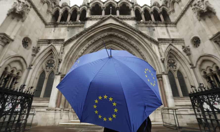 A person under an EU flag umbrella outside the high court in London.
