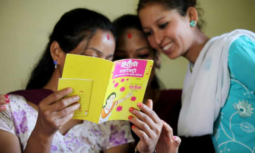 Young women read a leaflet about sex education and women's empowerment in Sankhu community clinic, Nepal.
