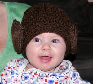 Smiling baby wearing a brown crochet hat