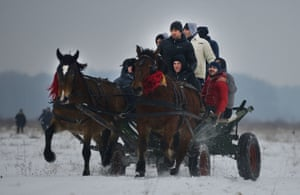 People on a horse carriage take part in a traditional Epiphany celebration in the village of Pietrosani, Romania. Each year, horse owners and their animals gather on a field next to the village to be blessed by an Orthodox priest and to take part in a race