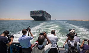 Journalists on a nearby boat film the Panama-flagged MV 'Ever Given' container ship sailing along Egypt's Suez Canal near the canal's central city of Ismailia on July 5, 2021.