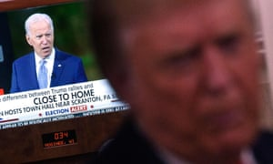 An image of Joe Biden is seen on a TV as Donald Trump speaks to reporters onboard Air Force One.