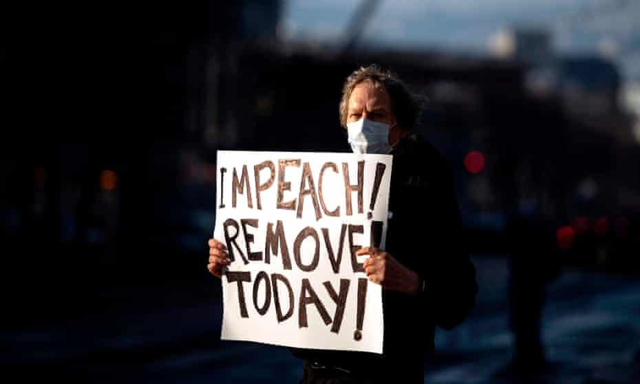 Protester Kenneth Lundgreen holds up a sign calling for the impeachment of President Donald Trump as police put together barricades outside Twitter corporate headquarters in San Francisco, California.