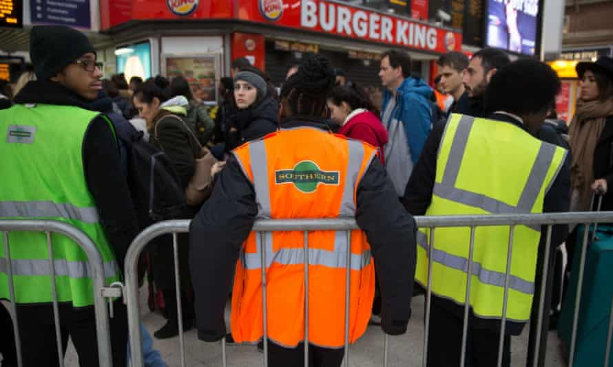 Commuters queue to take a train to Gatwick as strike action affects service at Victoria station in London.