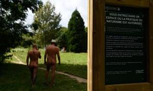 Two men walk past a sign at the Bois de Vincennes park