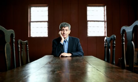 carl zimmer seated at a long and antique oak dining table with two leaded windows at his back