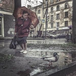 Woman by a rain puddle.