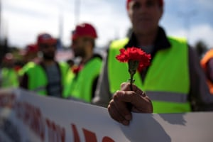 Athens, Greece. A member of the communist-affiliated PAME holds a carnation during a rally