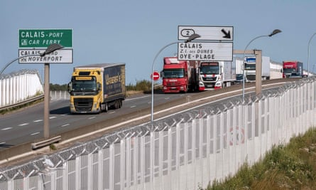 Lorries drive along a protection fence, preventing access to a circular road leading to the port of Calais