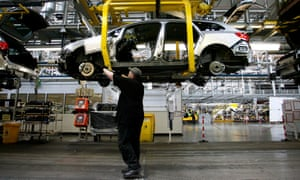 An employee works under a Vauxhall Astra car on the production line at Ellesmere Port