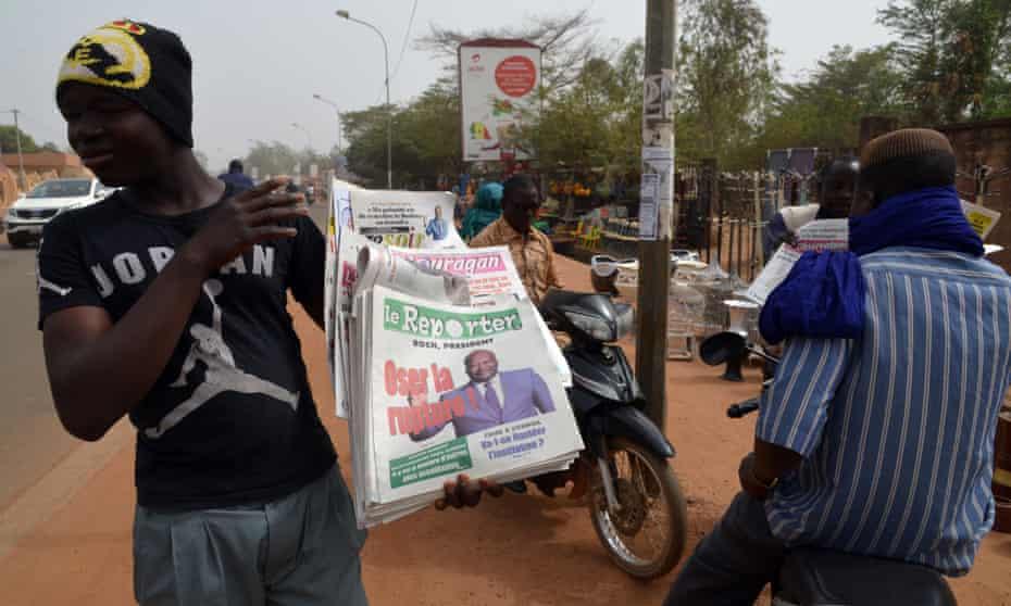 A street vendor sells newspapers in Ouagadougou on 3 December