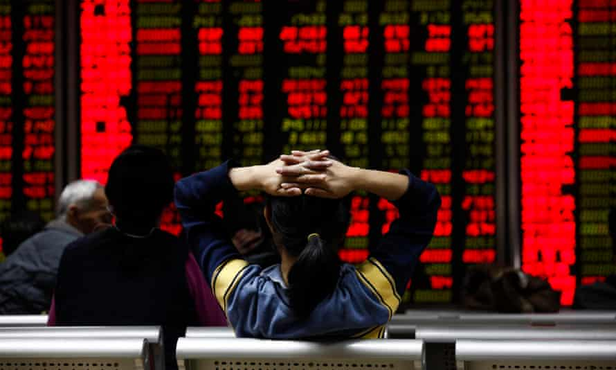 An investor views stock market data at a securities brokerage house in Beijing on Friday.