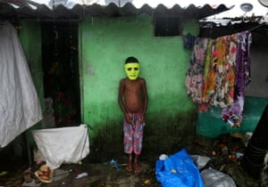 A boy takes shelter from the monsoon outside his house in Mumbai, India