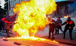 Police officers try to avoid the flames from a petrol bomb during an anti-government protest in Tirana, Albania