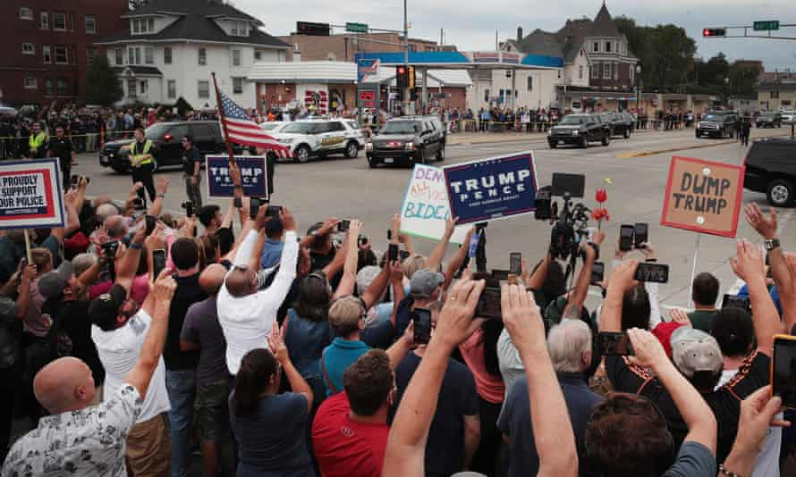 Trump supporters and protesters watch as the motorcade carrying Donald Trump passes by in Kenosha, Wisconsin.