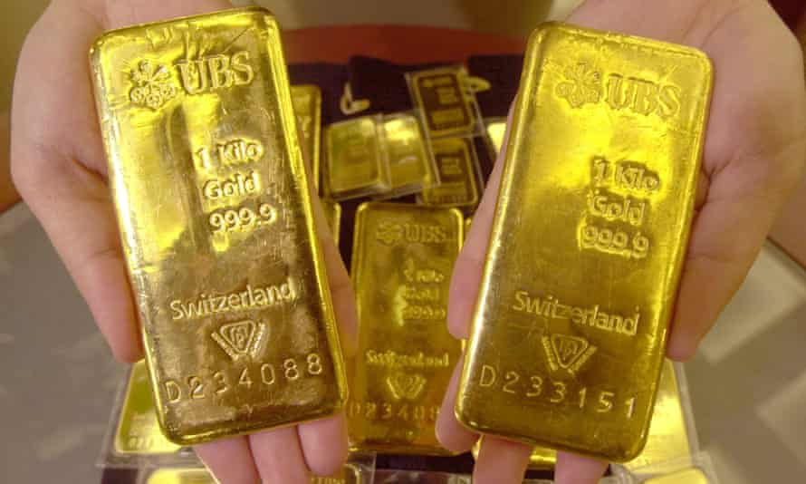 An employee shows gold bars at Shinhan Bank in Seoul