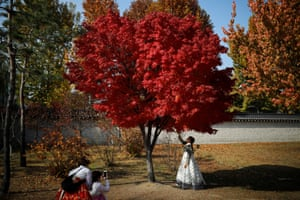 Women wearing traditional Hanbok dress pose for photographs on an autumn day at Gyeongbokgung Palace in Seoul