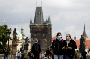 People wearing face masks walk across the medieval Charles Bridge in Prague, Czech Republic, September 25, 2020.