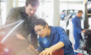 Mechanics working on engine in auto repair shop.