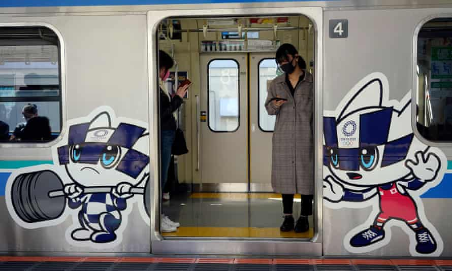 Commuters wearing face masks stand in a train decorated with Tokyo Olympic and Paralympic Games mascots in Tokyo, Japan. Japan is considering vaccinating Olympic athletes ahead of the rest of the population.