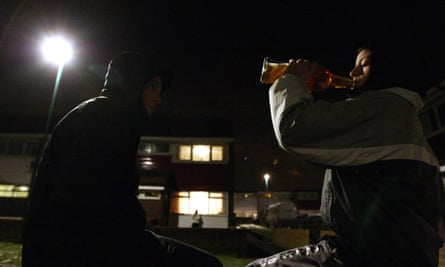Teenagers drink alcohol on a street corner